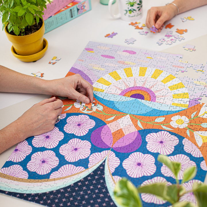 Hands put together puzzle pieces on same flower-themed puzzle