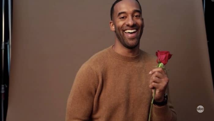Matt James laughing while holding a rose