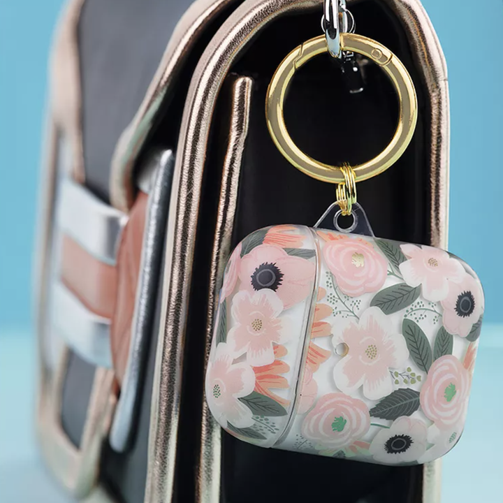 Floral Rifle Paper Co AirPods case clipped onto small clutch