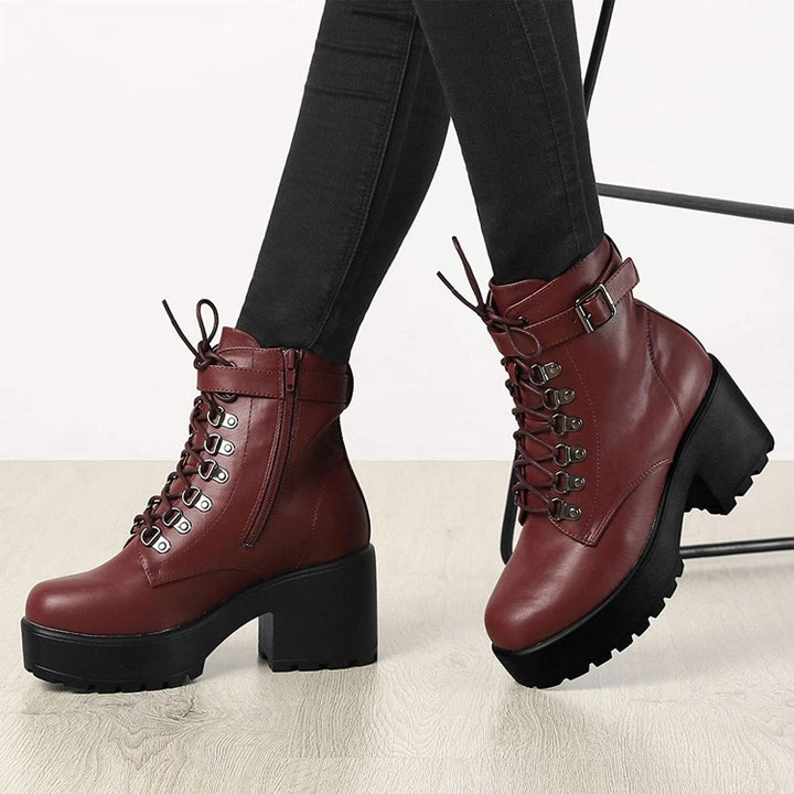 A model wearing the low-heel lace-up booties in burgundy and black