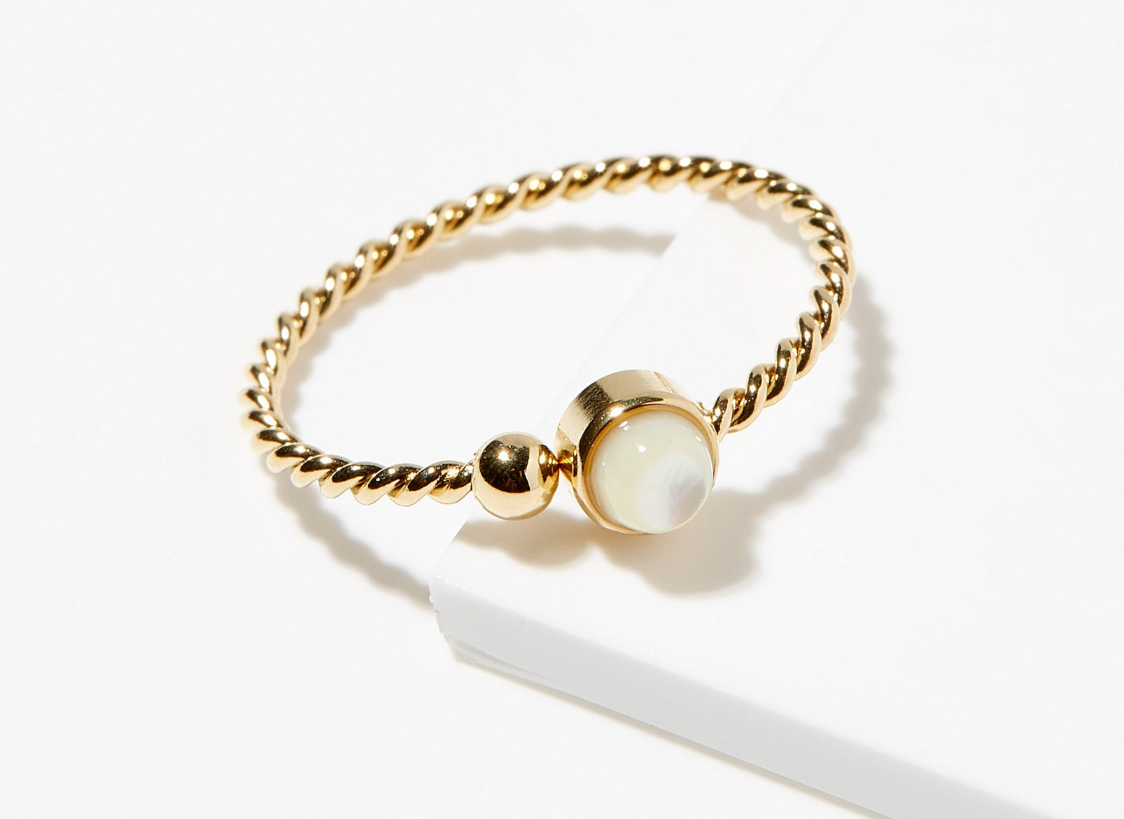 A small gold ring with a pearl jewel at the center