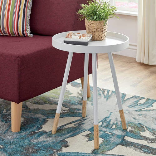 The table in white, with a rounded tabletop, splayed legs, and natural wood tone at the bottom of each leg