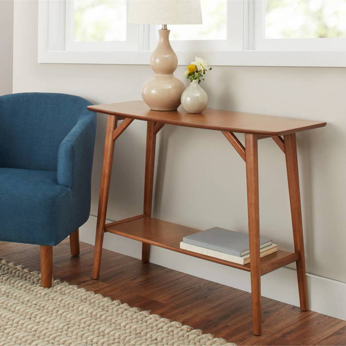 The table, which has long, thin, rounded legs, an open storage shelf near the bottom, and a rectangular top