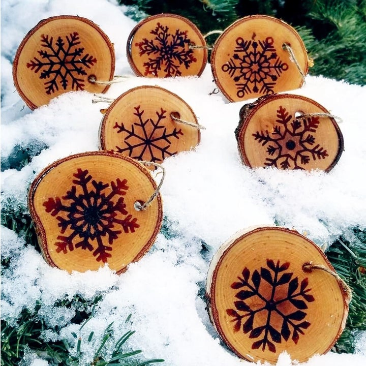 a reviewer's wooden ornaments with snowflakes etched onto them from the cricut