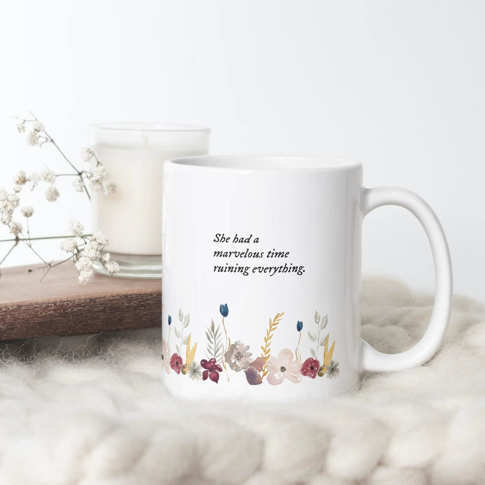 "A white mug with watercolor flowers on the bottom that says ""she had a marvelous time ruining everything"""