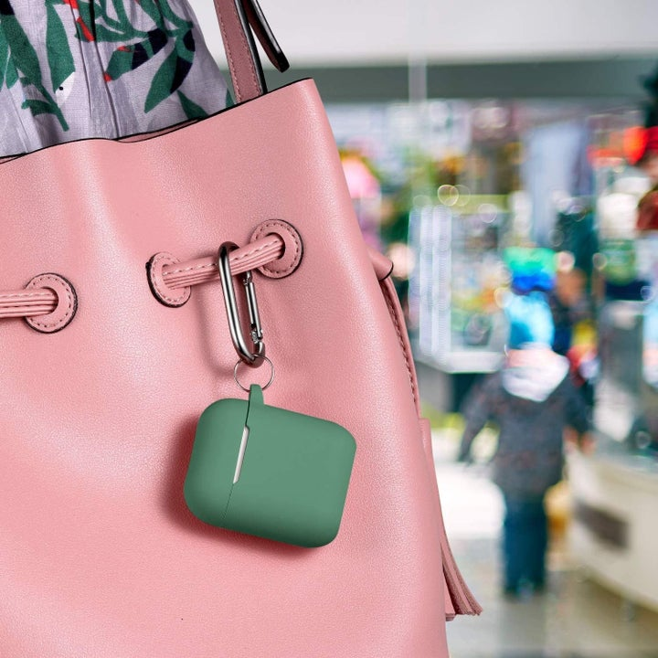 Airpods in green silicone case clipped on to handbag with carabiner clip