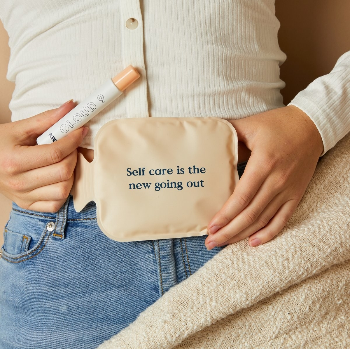 """Model holds heat-pack that says """"Self care is the new going out"""" and Cloud 9 essential oil blend bottle"""