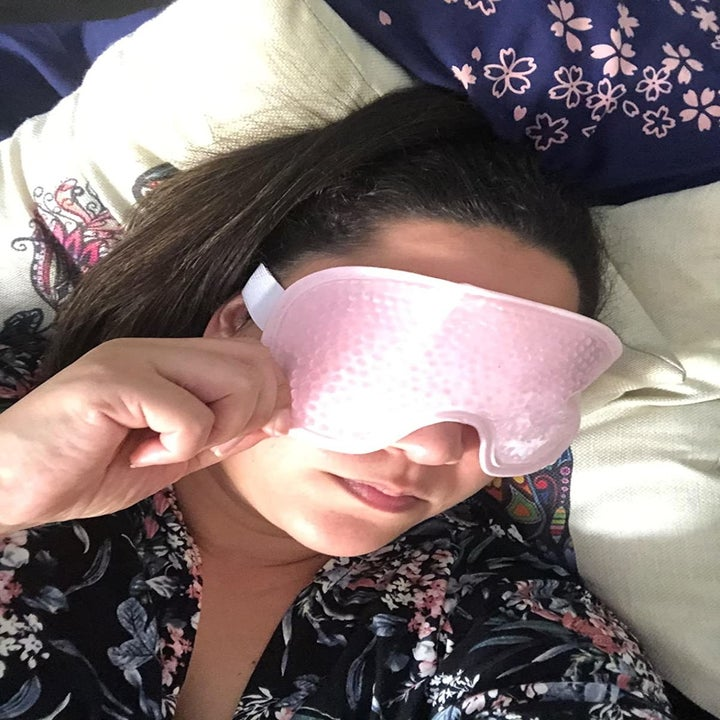 Reviewer wears pink cooling eye mask while lounging on a bunch of pillows