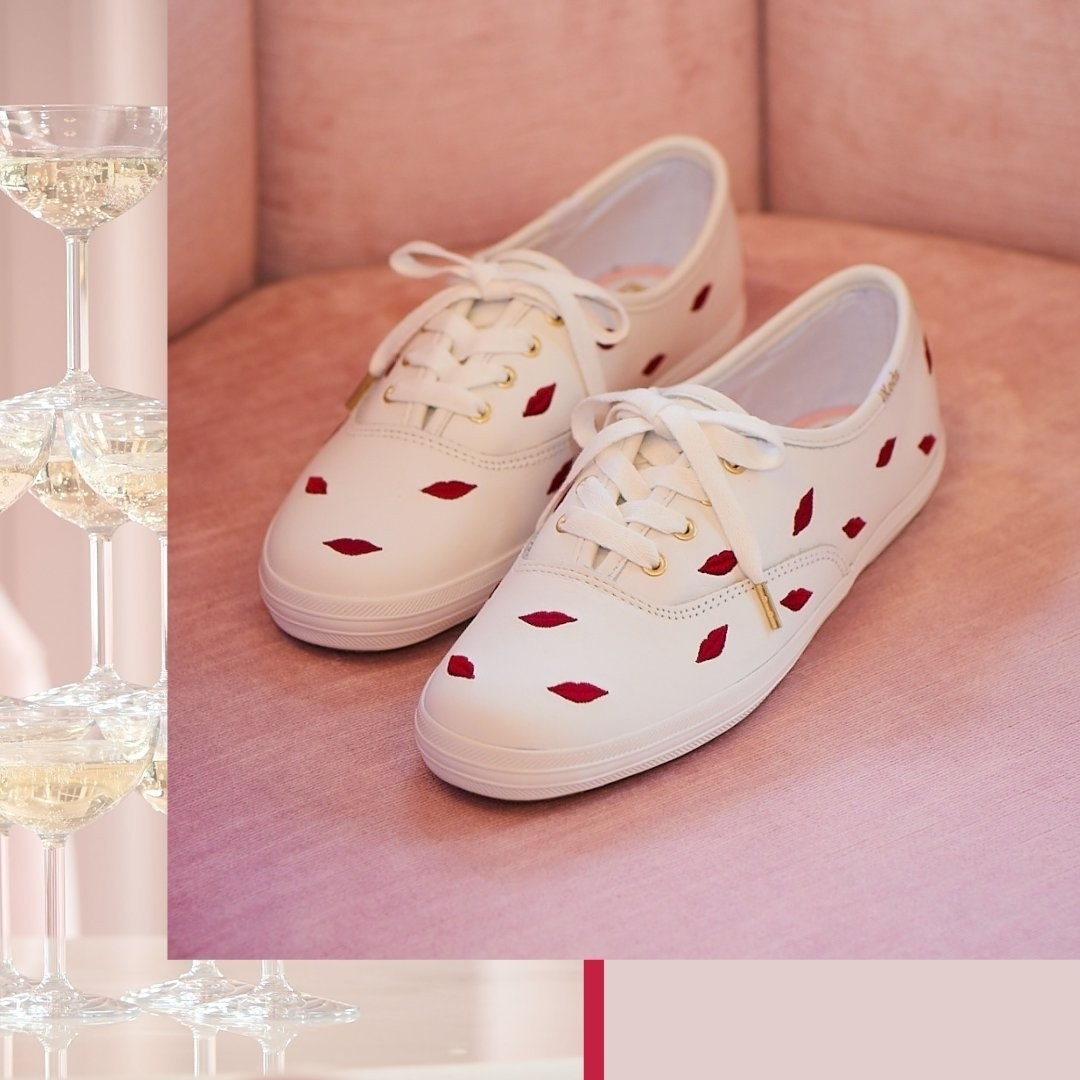 A pair of tennis shoes with embroidered lips all over the top and sides