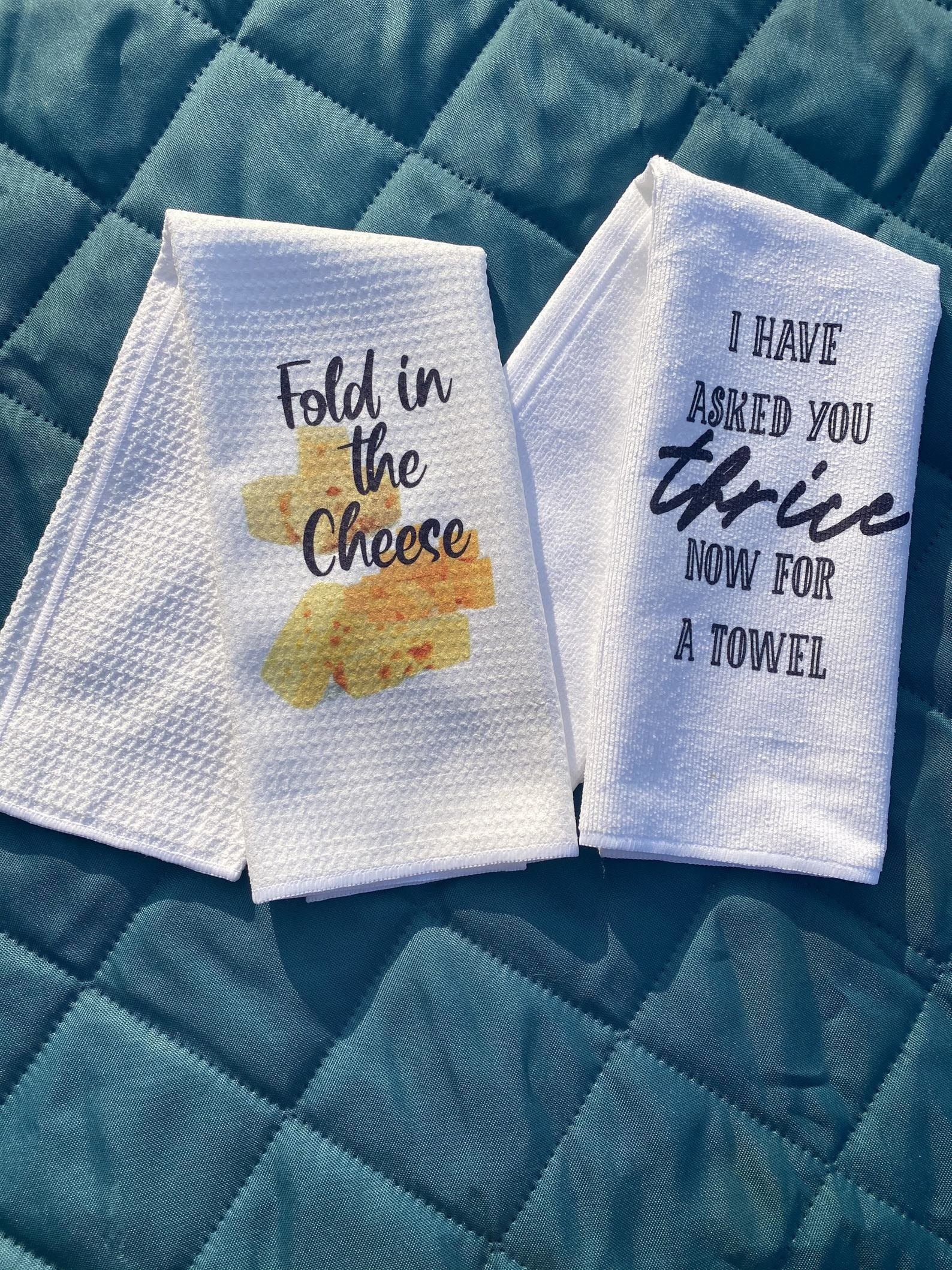 "One towel that reads ""Fold the Cheese"" with cheese graphics, and another towel that reads ""I HAVE ASKED YOU THRICE NOW FOR A TOWEL"""