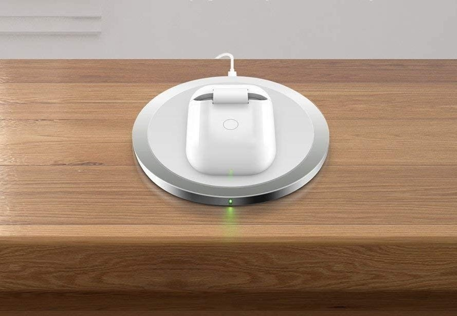 AirPods placed in wireless charger case on wireless charging pad