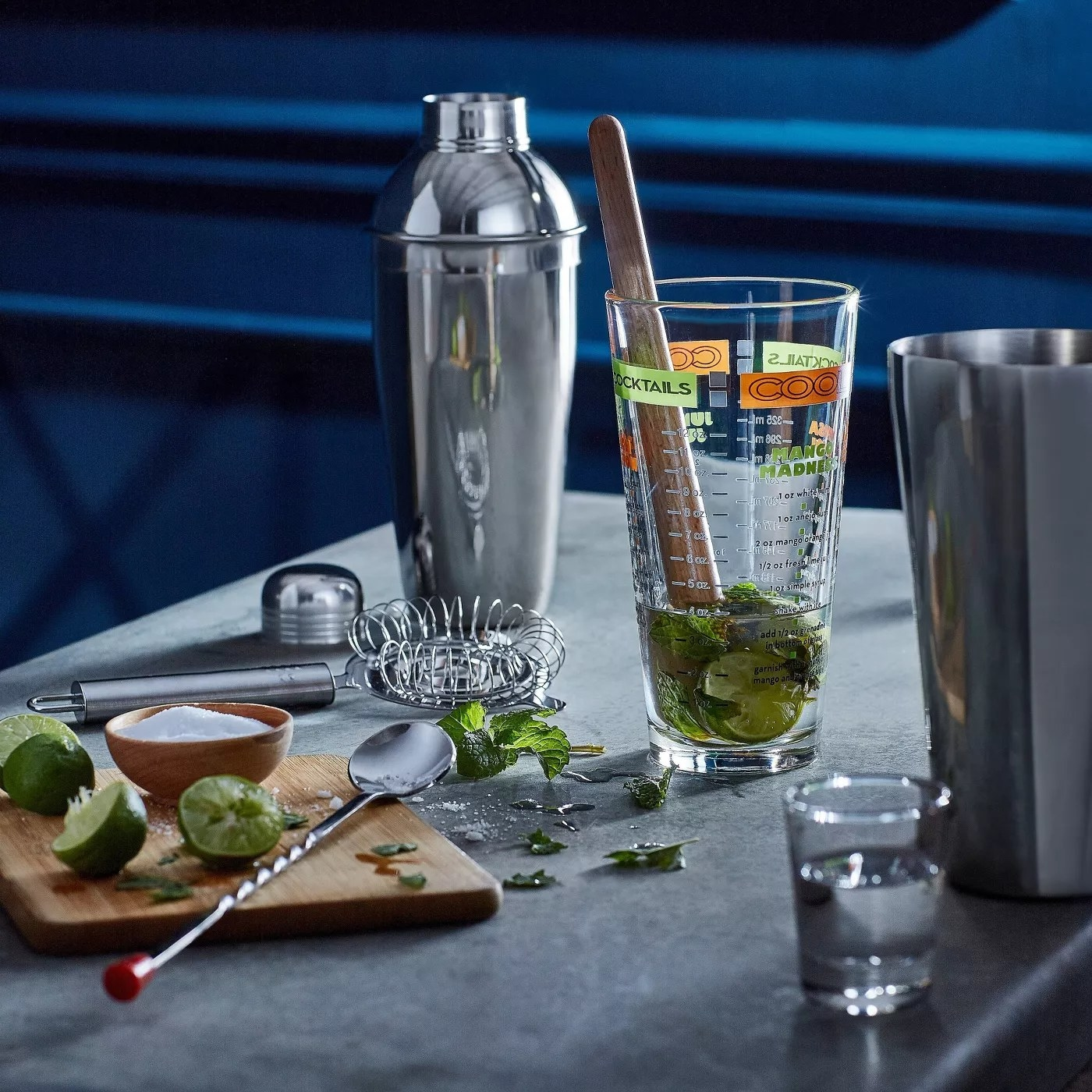 A shot glass, a glass mixing glass, a metal strainer, a bar spoon, a wooden muddler, a metal shaker base, and a metal boston shaker