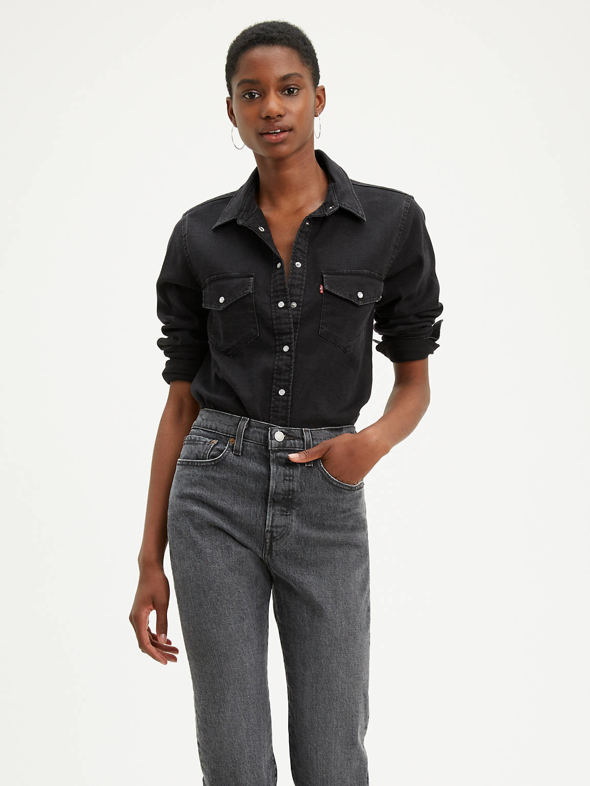 a model wearing the shirt in black with a pair of dark-colored jeans
