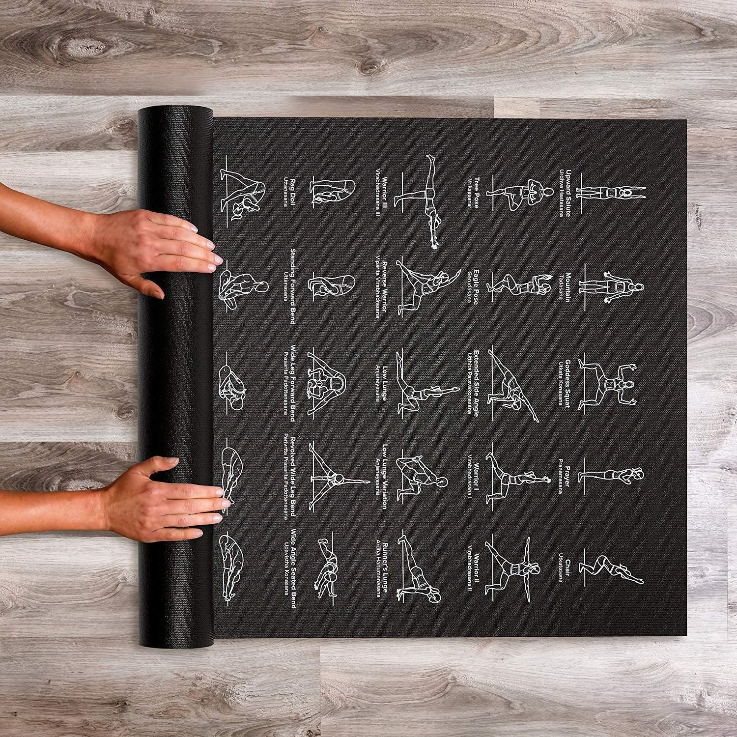 Hands roll out black yoga mat with white illustrated yoga poses