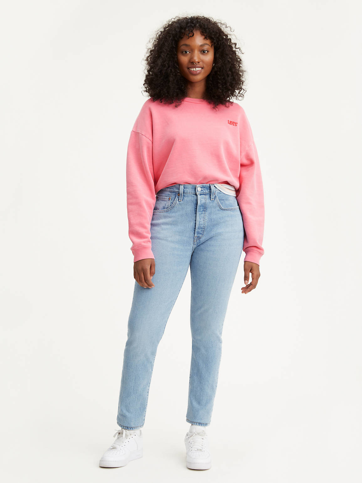 a model wearing the light-wash straight jeans with a pink sweater