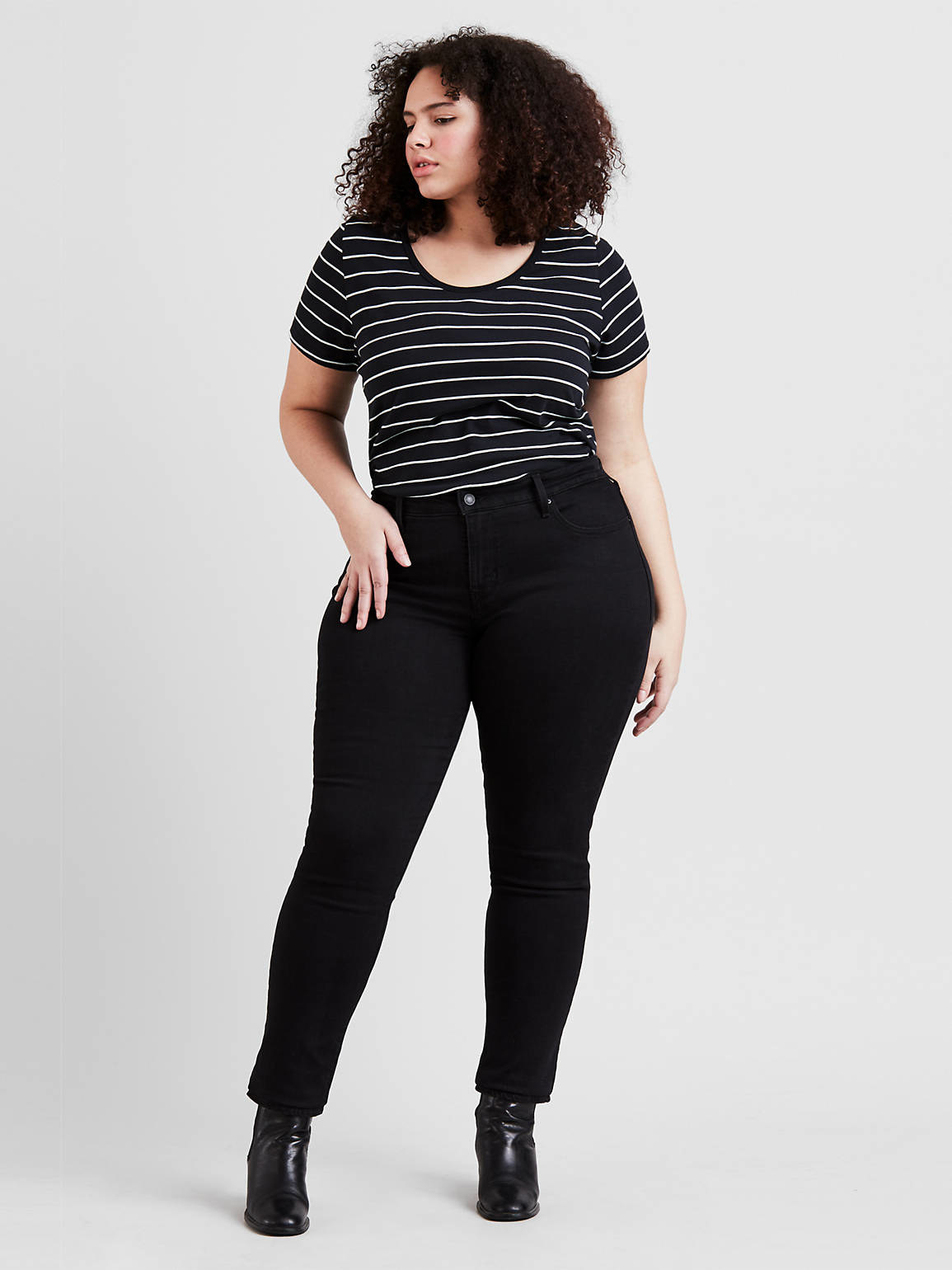 a model wearing the jeans in black with a striped shirt and booties