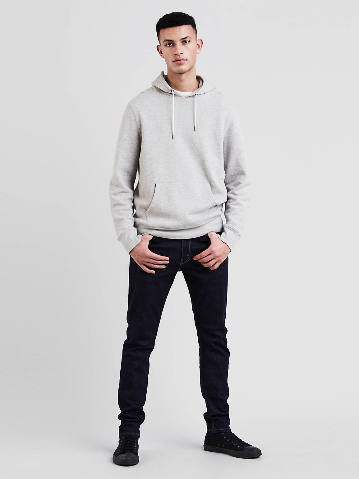 a model wearing the pants in dark hollow wash