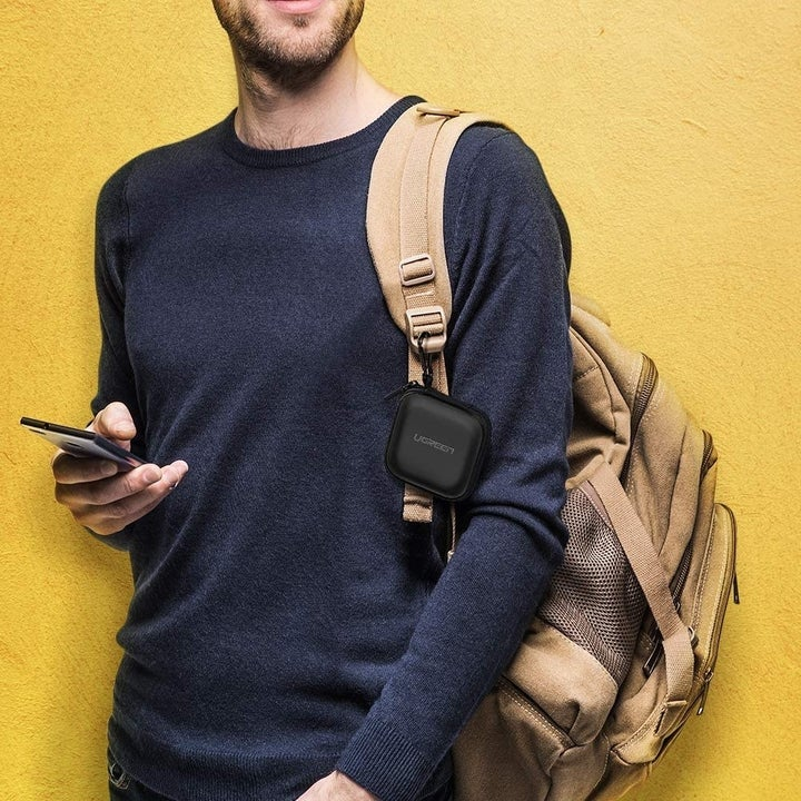 Model with zipped up case attached to backpack strap