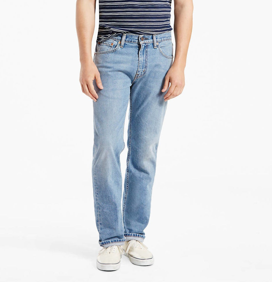 a model wearing the jeans in clif wash with white shoes