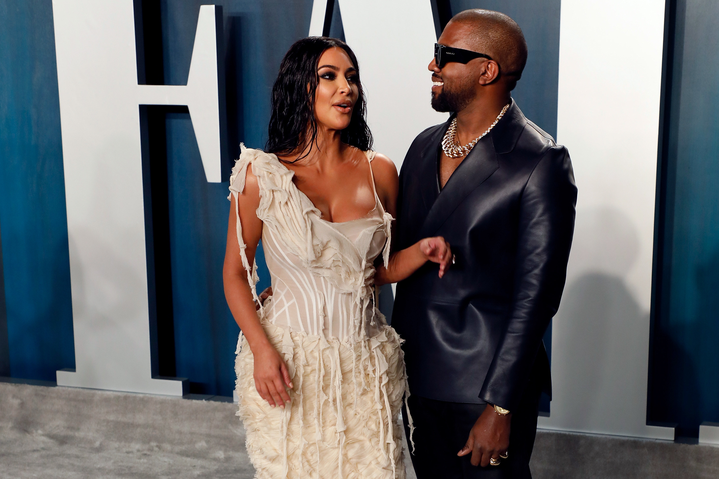 Kim Kardashian and Kanye West wear fashionable outfits in front of a Vanity Fair sign