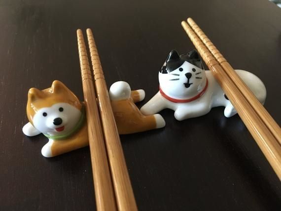 The dog and cat versions of the chopstick holders holding chopsticks