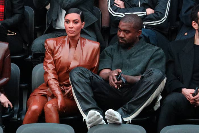 Kardashian wears a fashionable leather bodysuit, sitting next to Kanye, who has his feet up on the chair in front of him