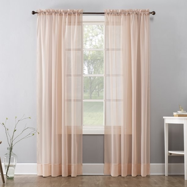 The curtain, which hangs to the floor and is peach-colored, but sheer