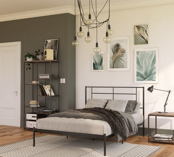 The bed frame, which is metal, in black, with a wiry geometric design in the headboard