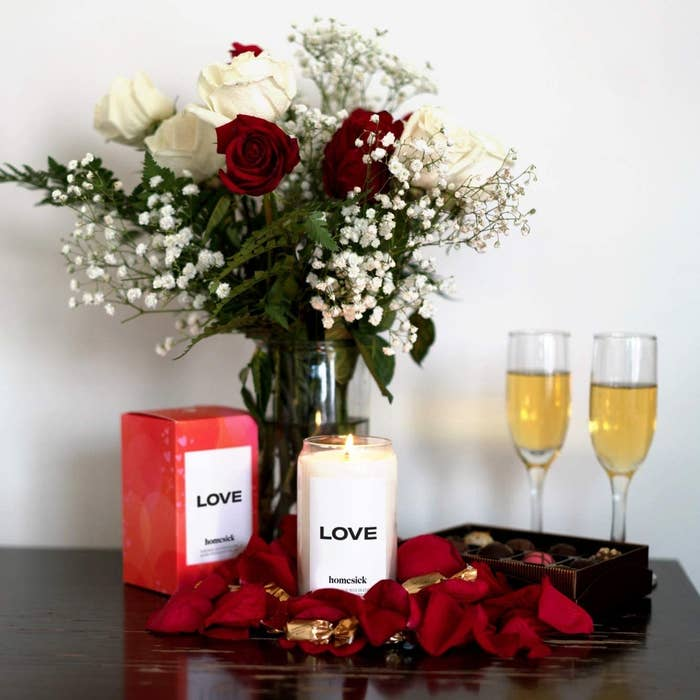 love candle next to box, vase of roses, and two champagne flutes