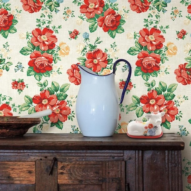 The wallpaper, which has red blooming flowers and stems on a cream background