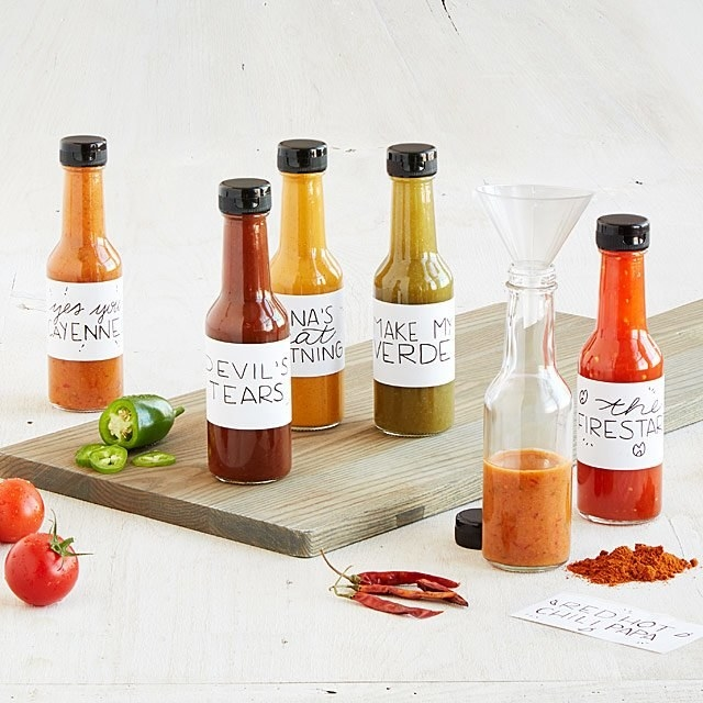 various DIY hot sauce bottles and peppers on a table with
