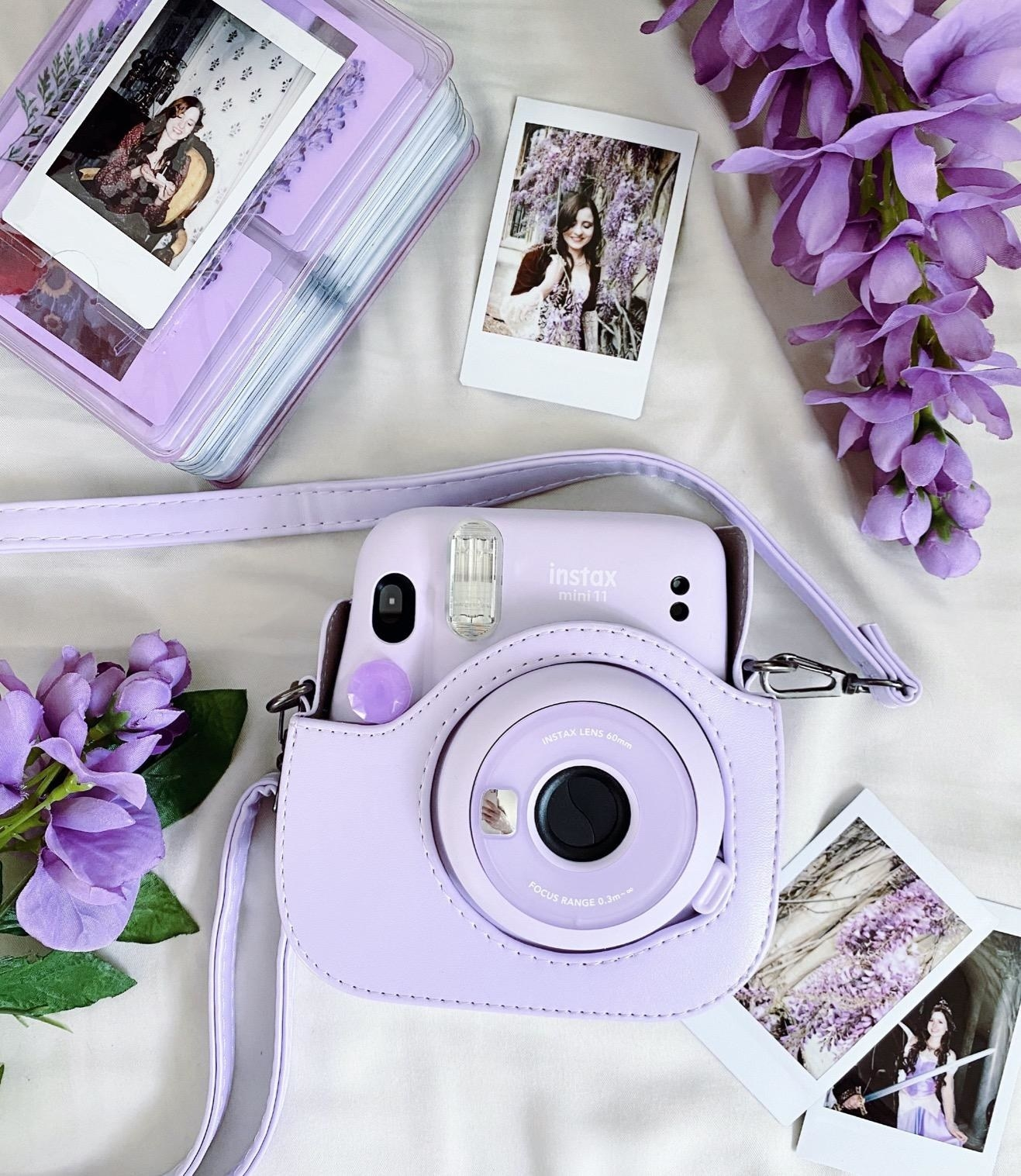 lavender instax camera inside a case laid next to photo prints and flowers