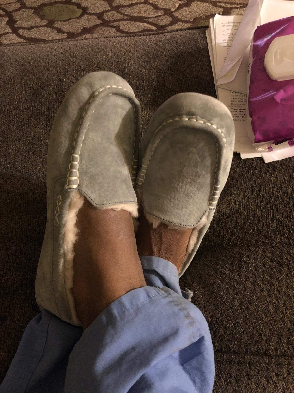 grey UGG moccasin slippers on crossed feet