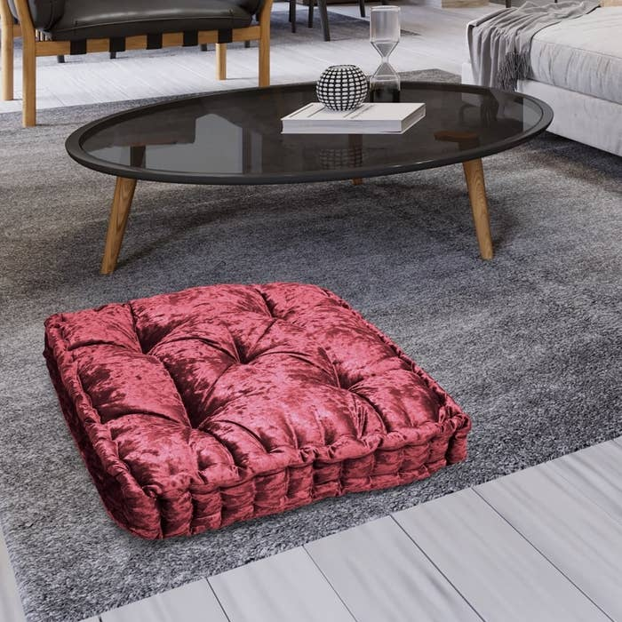 a crushed red velvet floor pillow on the floor in a living room