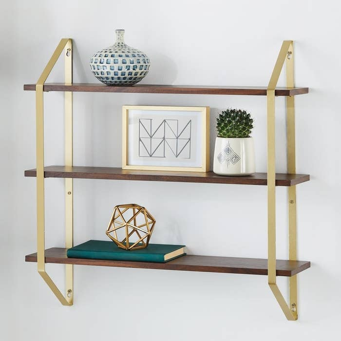 three wooden shelves with gold harware hanging on a wall