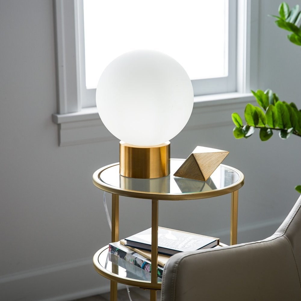 a white orb lamp with a brass cylindrical base