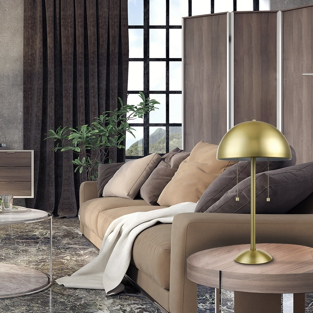 a brass lamp with a brass shade sitting on an end table in a room