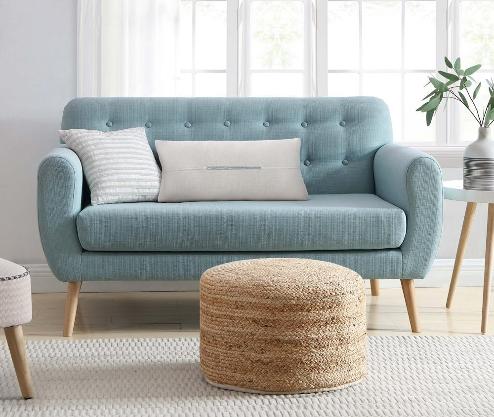 a woven bamboo pouf sitting at the base of a couch