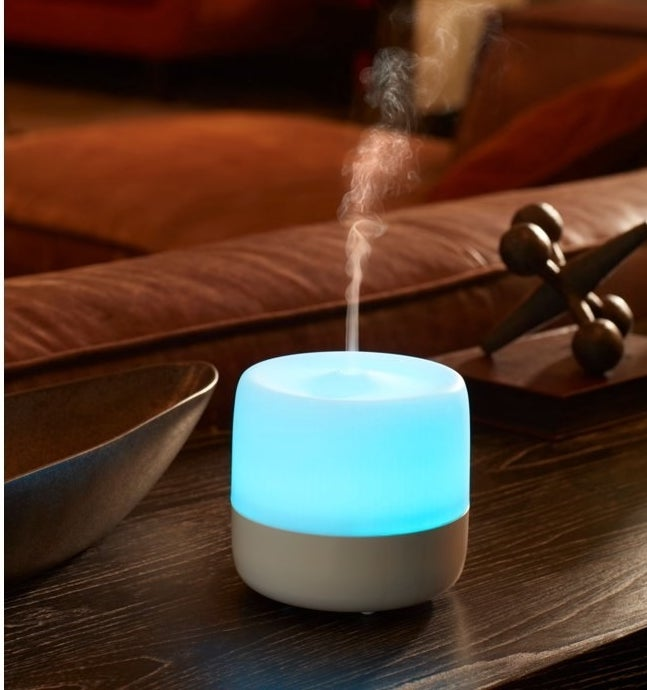 a white, lit diffuser diffusing essential oil mist in the air, sitting on a table
