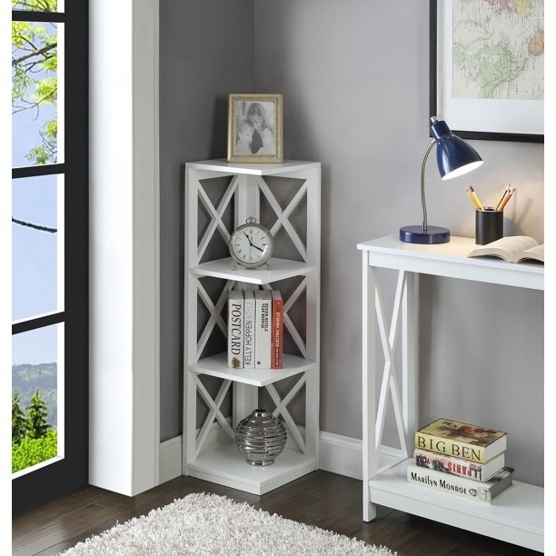 "The bookshelf in white, with four shelves for items, and two walls with open weave ""X""-shaped supports"