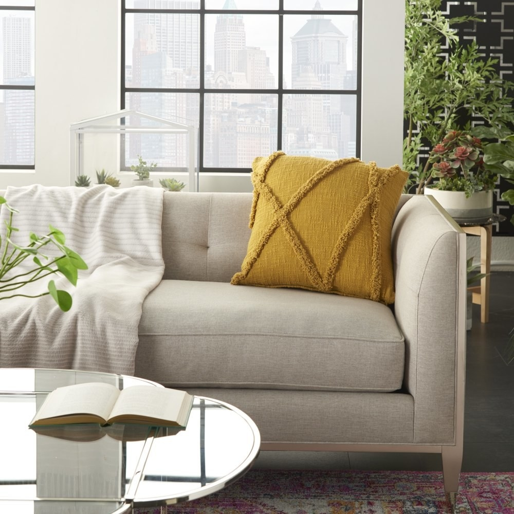 a mustard throw pillow at the edge of a couch
