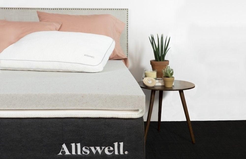 a grey mattress topper on top of a mattress in a bedroom