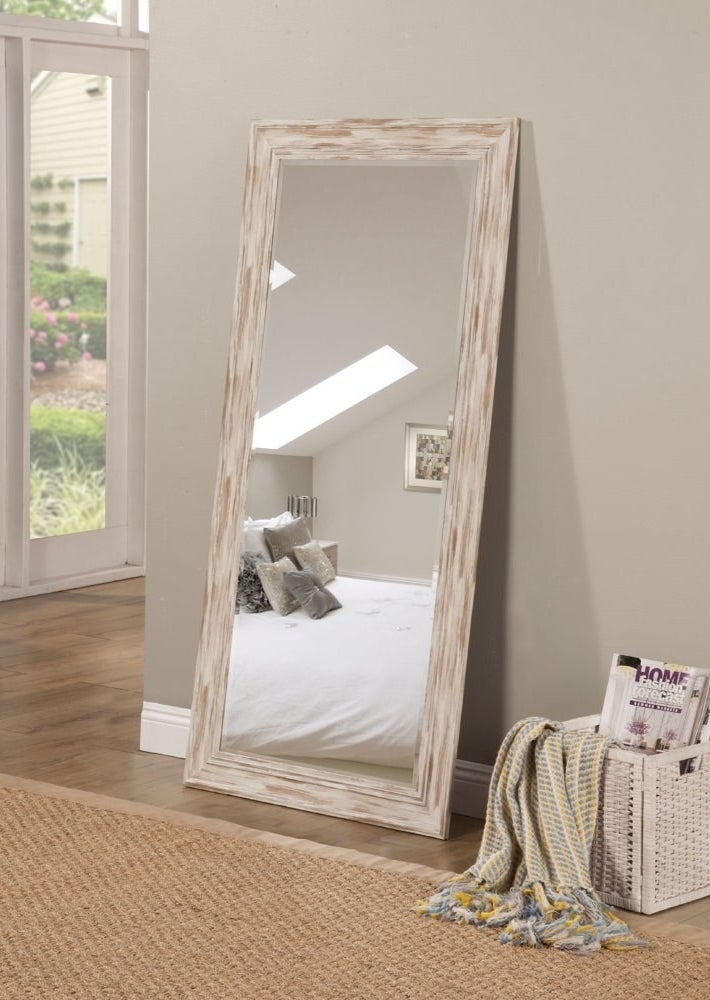 A full-length mirror resting on the floor. The mirror's frame is white and brown wood