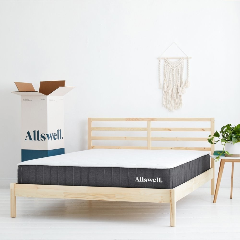 a white matress with grey edges on a bed, next to the box it comes shipped in