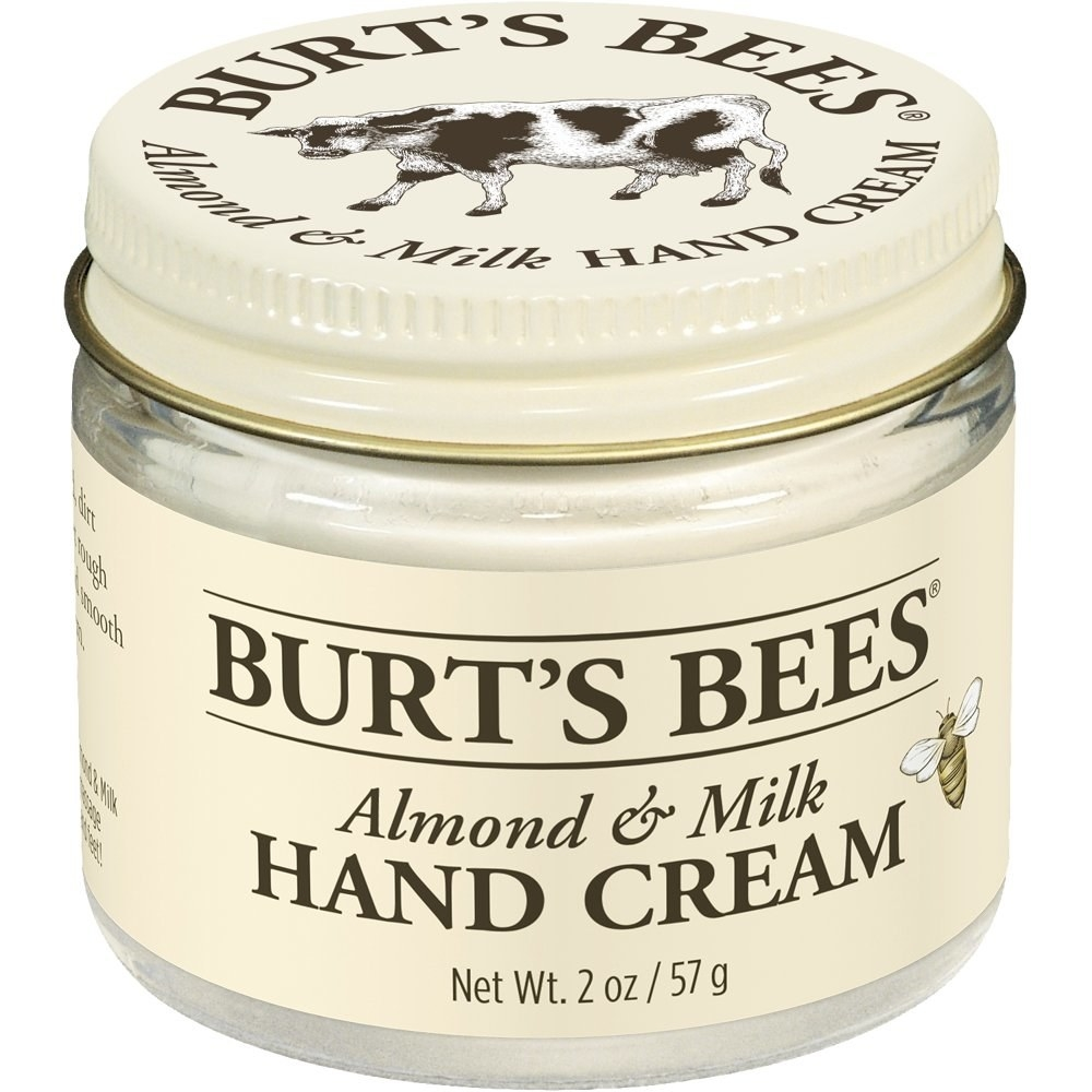 """a glass jar with a label that reads """"burt's bees almond and milk hand cream"""""""