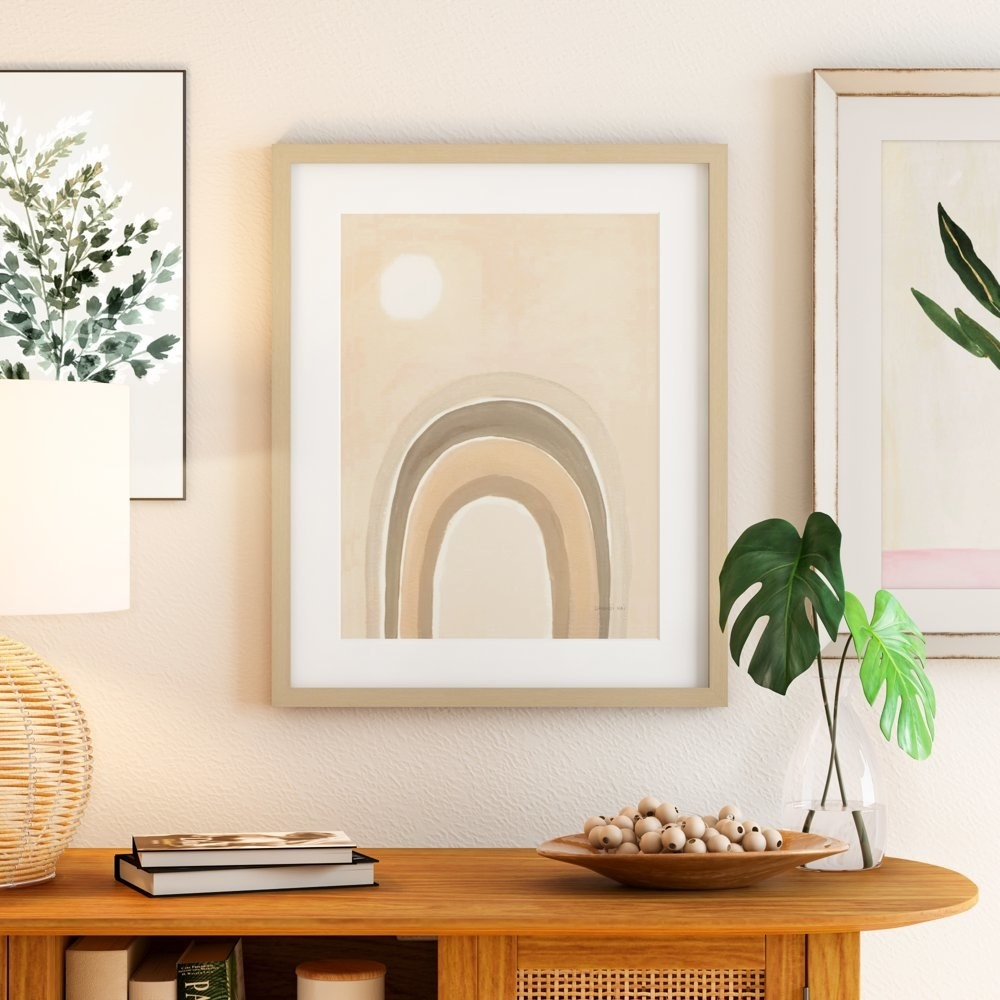 A framed art print with beige and tan colors in its design hanging on a wall