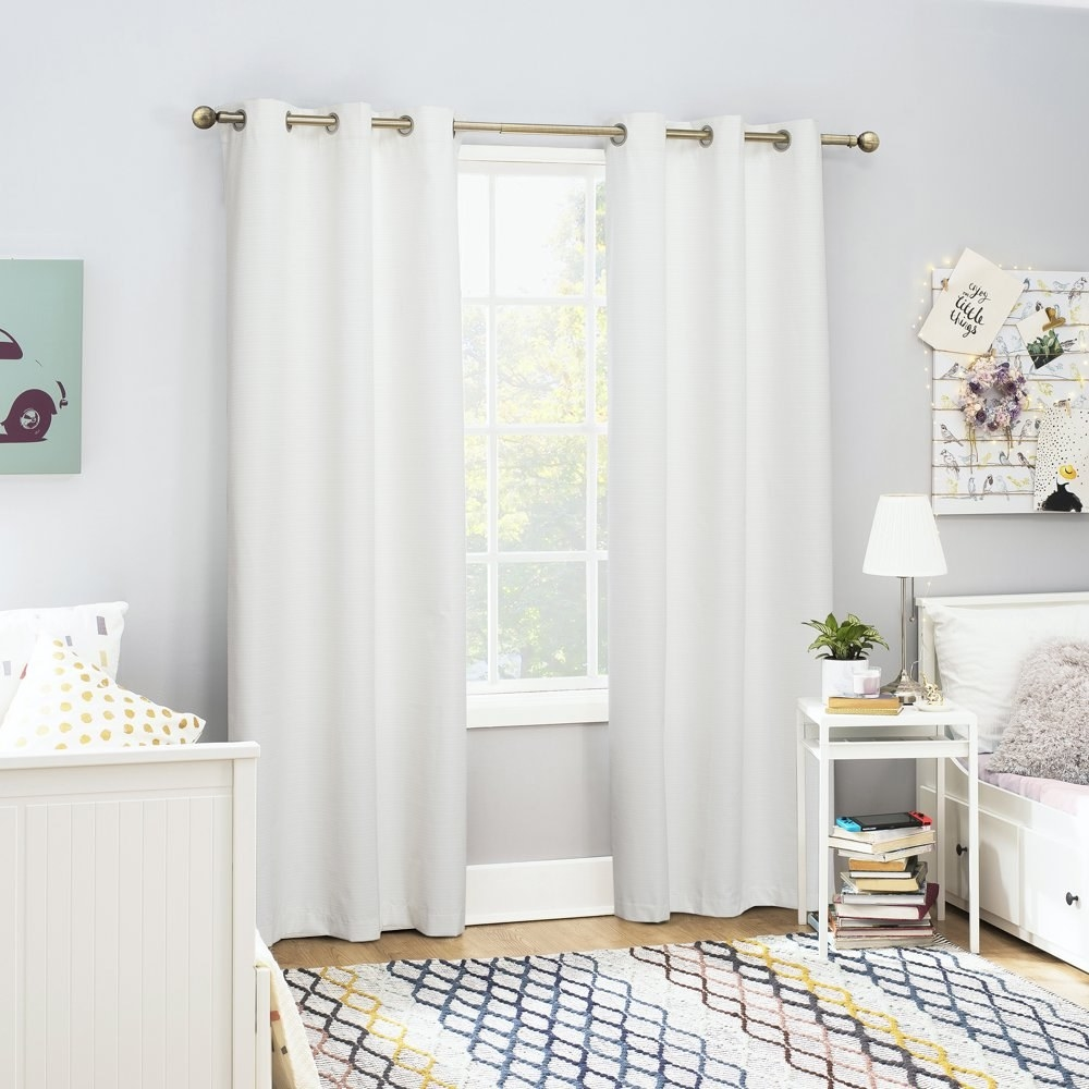 a pair of white curtains hanging in front of a window in a bedroom