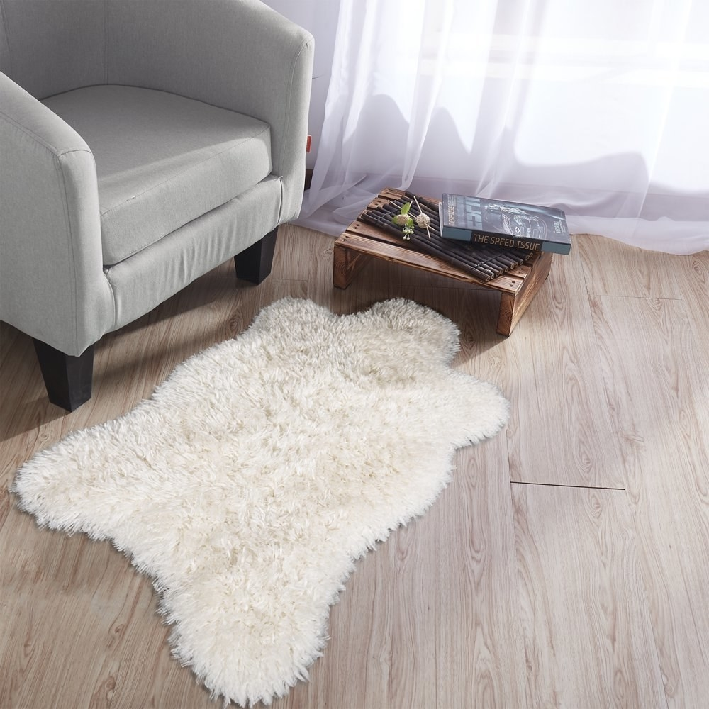 A white faux sheepskin area rug in front of a reading chair