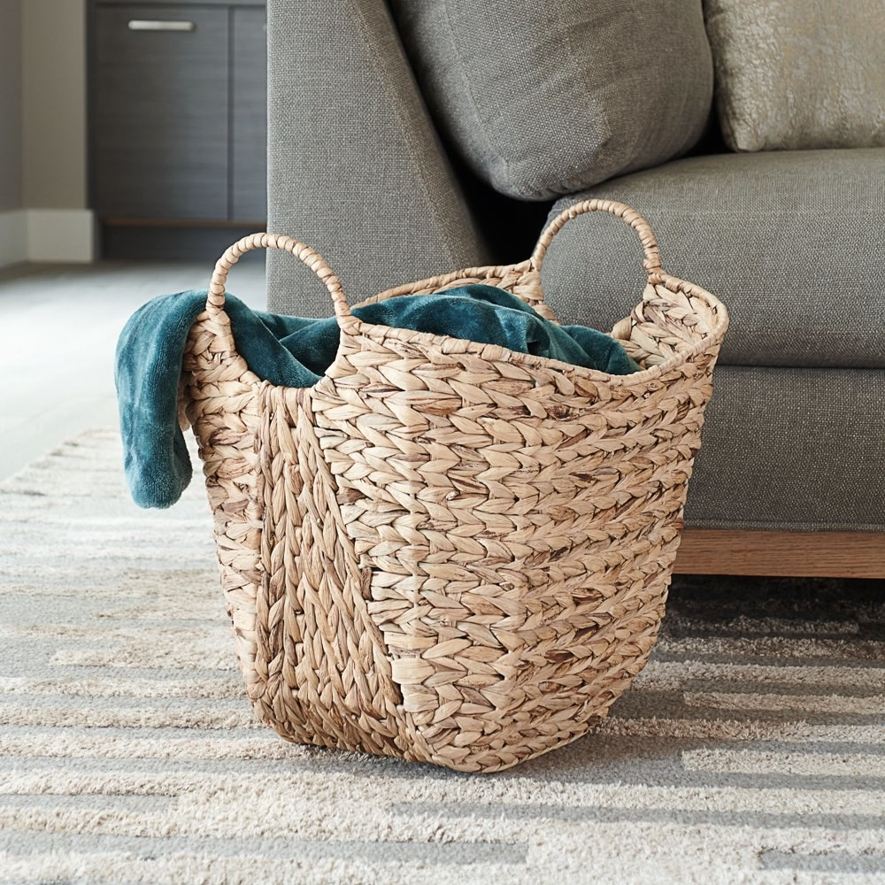 a tan wicker basket with two handles on either side holding a blanket