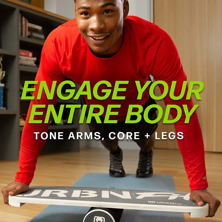 "Model balancing on board with arms in planking position with graphic saying ""engage your entire body"""